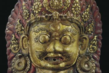 A GILT-COPPER REPOUSSE MASK OF BHAIRAVA