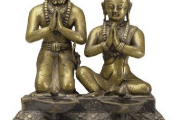 A brass ritual lamp with figures of a King and Queen