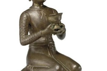A copper figure of a kneeling donor