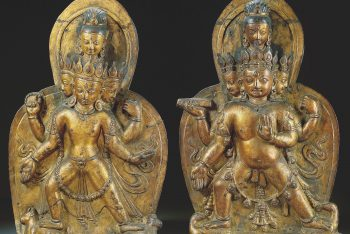 TWO GILT-COPPER REPOUSSE ORNAMENTAL PLAQUES DEPICTING SHIVA AND BHAIRAVA