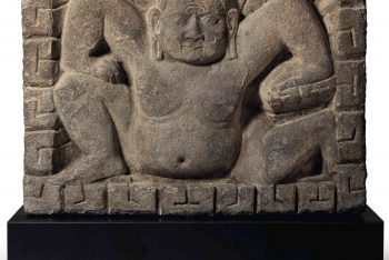 A BLACK STONE RELIEF OF A CROUCHING GANA