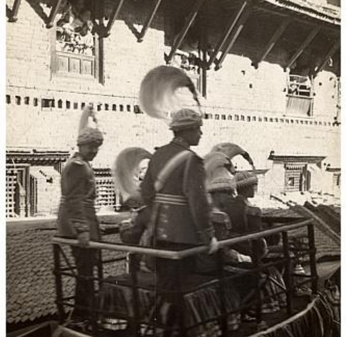 Men in uniform with large plumed hats on elephant